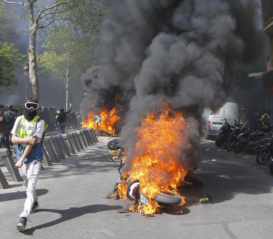 Un hombre corre junto a una motocicleta en llamas durante una protesta de chalecos amarillos en París. (AP/Michel Euler) (semisquare-x3)