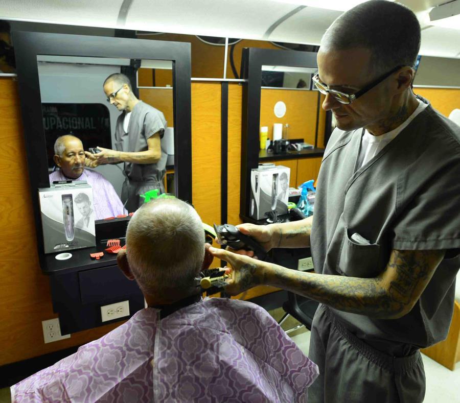 Un confinado realiza un recorte de cabello a bordo de la guagua del programa