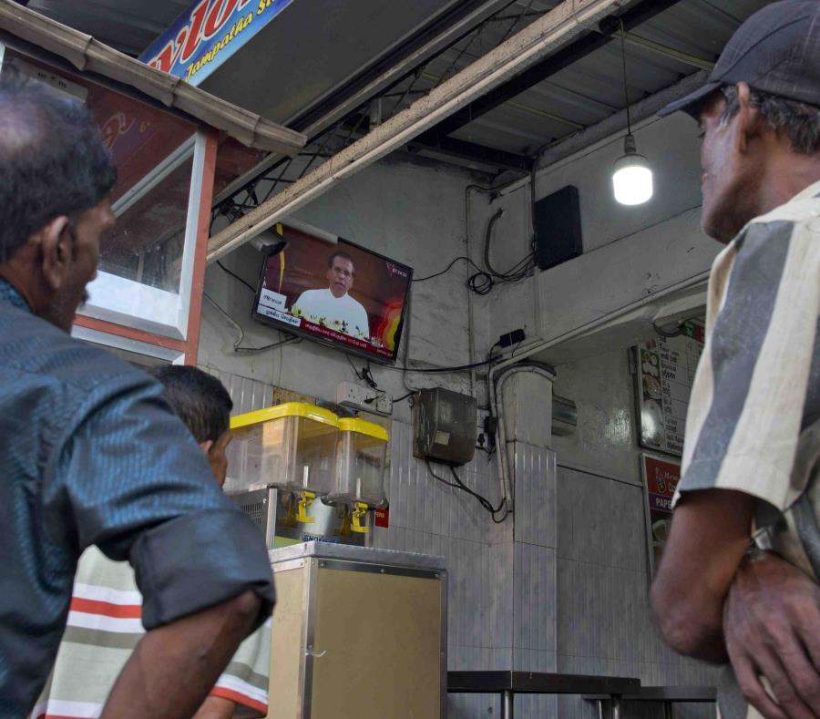 Ciudadanos observan el mensaje del presidente de Sri Lanka, Maithripala Sirisena's, tras los atentados (semisquare-x3)