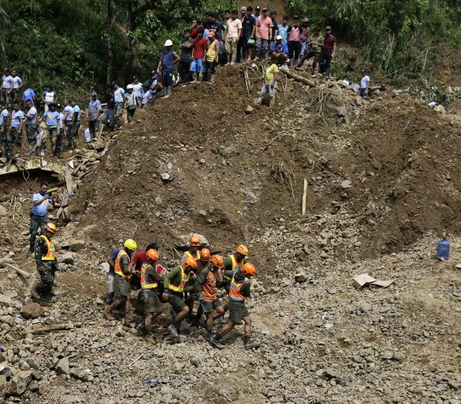 Socorristas recuperan el cadáver de una persona donde varias de ellas quedaron sepultadas debido a un alud de tierra y piedras después del tifón Manghkut que azotó Itogón, provincia de Benguet, en el norte de Filipinas. (AP) (semisquare-x3)