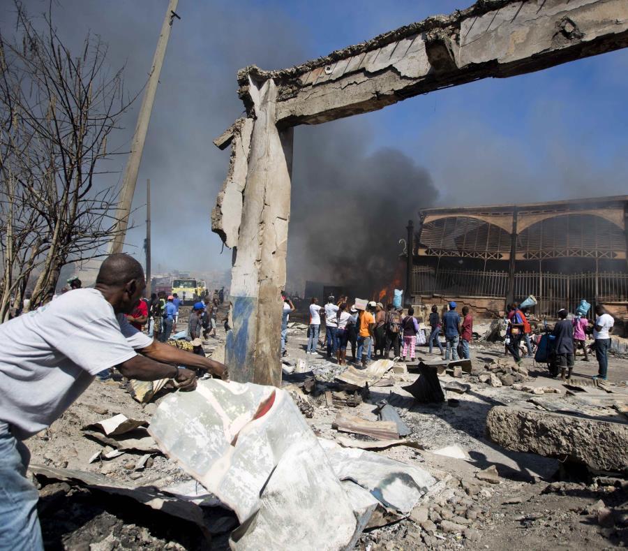 Un hombre busca objetos que aún sirvan luego de un incendio que arrasó una sección del Mercado de Hierro, en Puerto Príncipe, el martes 13 de febrero de 2018. (semisquare-x3)