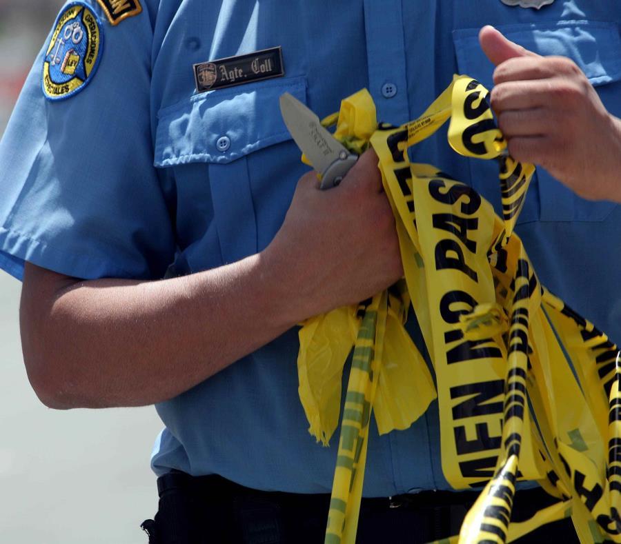 Un agente de la Policía investiga la escena de un asesinato. (GFR Media) (semisquare-x3)