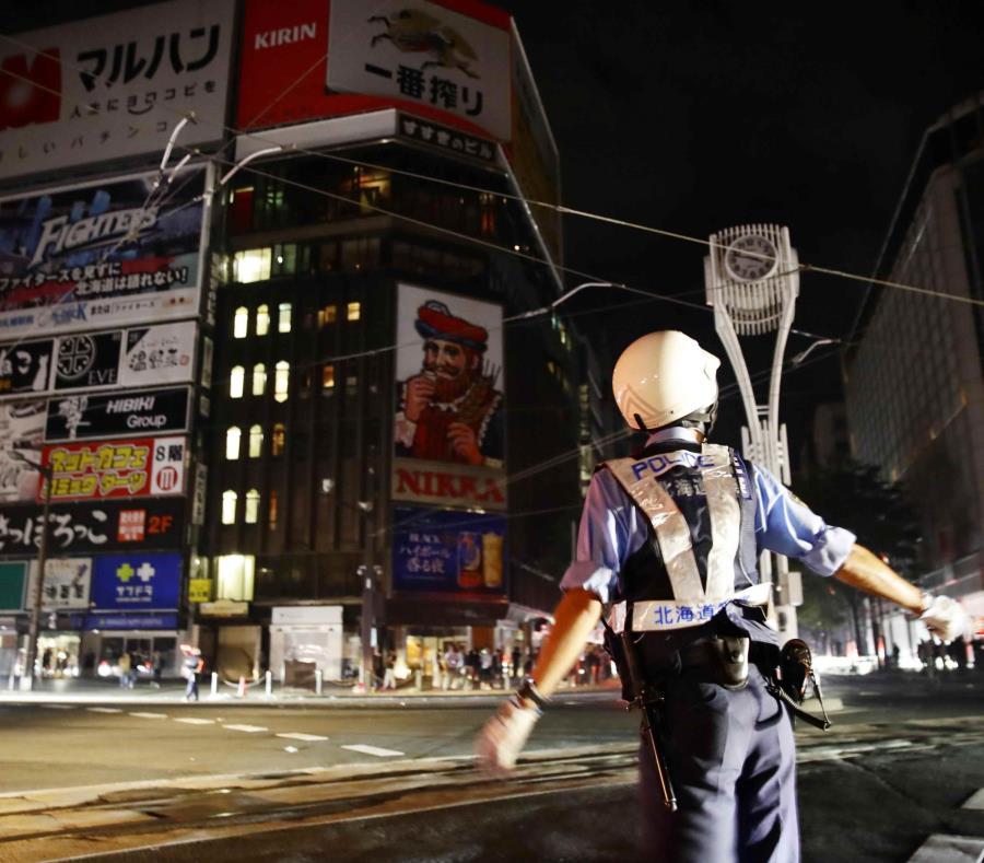 Un agente de policía controla el tránsito durante un apagón a causa de un fuerte sismo. (AP) (semisquare-x3)