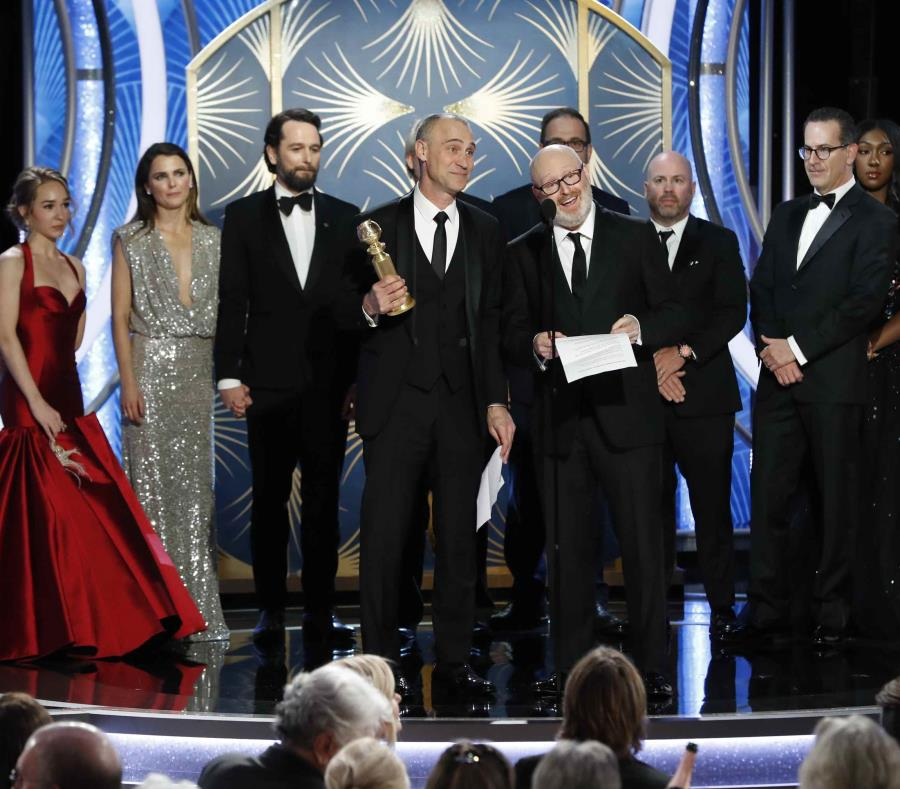 En esta imagen difundida por NBC, Joel Fields, en el centro, y Joe Weinberg, a su lado, reciben el Globo de Oro a la mejor serie de drama por