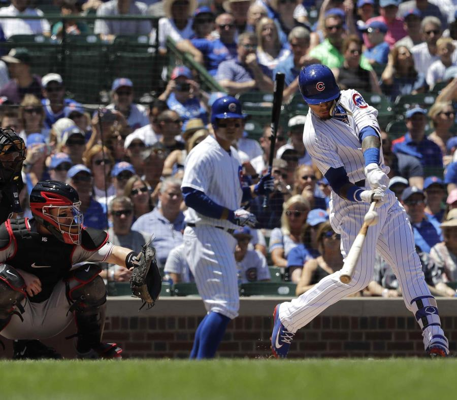 Chicago Cubs' Javier Baez, right, hits a double during the first inning of a baseball game against the Cincinnati Reds, Sunday, July 8, 2018, in Chicago. (AP Photo/Nam Y. Huh)Javier Báez, de los Cachorros de Chicago, pega un doblete durante la primera ent (semisquare-x3)