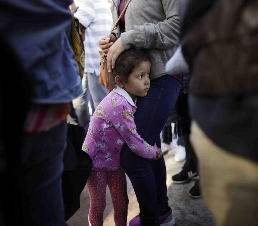Nicole Hernández, de Guerrero en México, se aferra a las piernas de su mamá mientras aguardan para solicitar asilo político en la frontera en los Estados Unidos mediante el cruce fronterizo en Tijuana. (AP / Gregory Bull) (semisquare-x3)