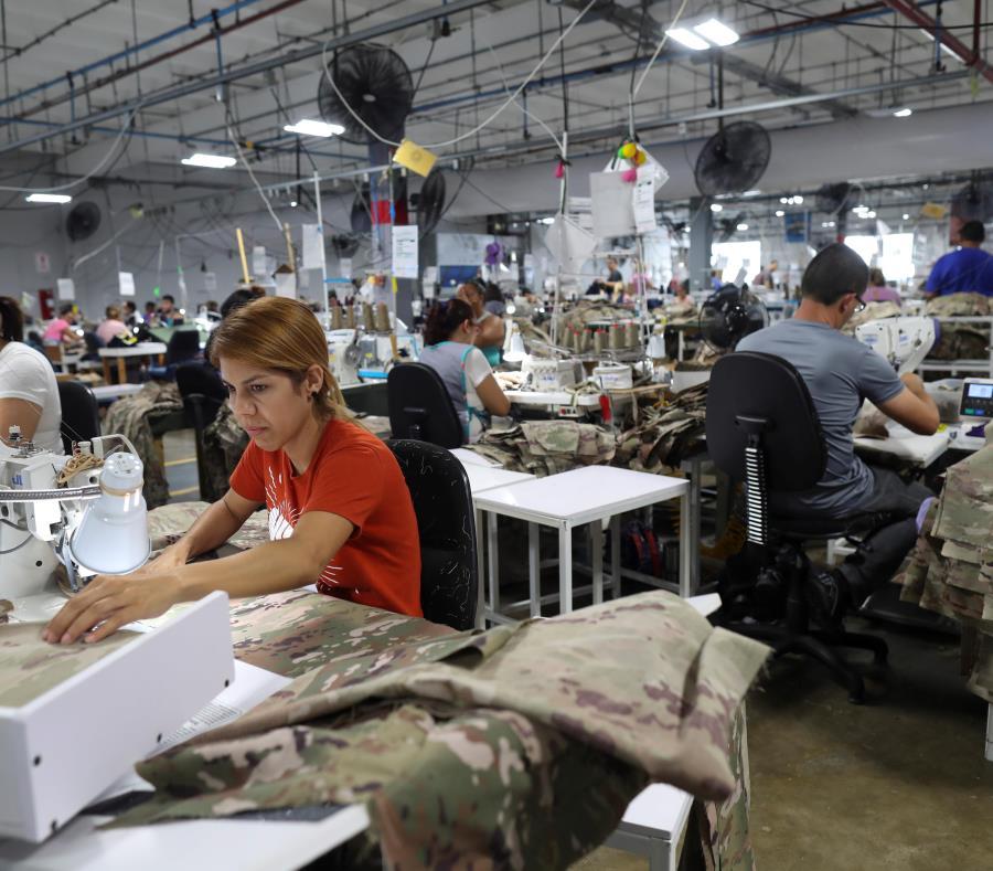 Anelis Jiménez (camisa roja) y otros empleados en la fábrica de SNC Technical Services, en Camuy. (semisquare-x3)