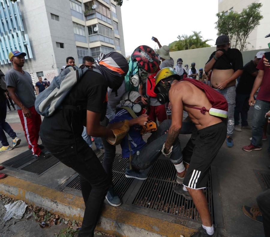 Manifestantes antichavistas ayudan a un herido, durante las manifestaciones contra el gobierno de Nicolás Maduro, en Caracas (semisquare-x3)