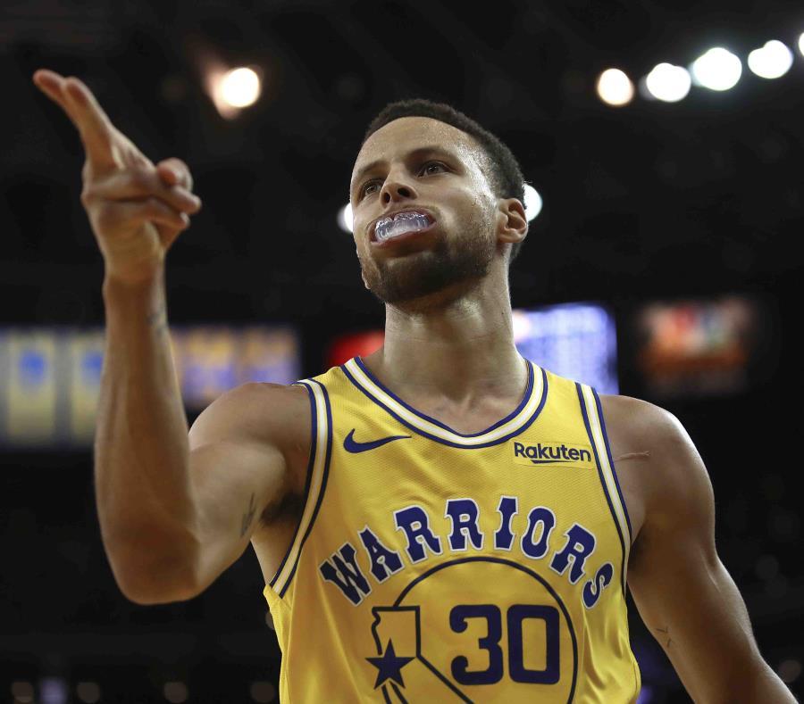 Stephen Curry apunta con dos de sus dedos luego de marcar un canasto en el desafío contra los Wizards de Washington. (AP / Ben Margot) (semisquare-x3)