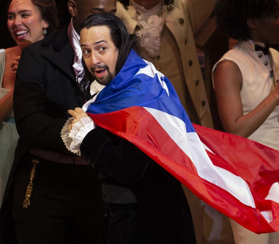 Lin-Manuel Miranda con la bandera de Puerto Rico sobre sus espaldas. (semisquare-x3)