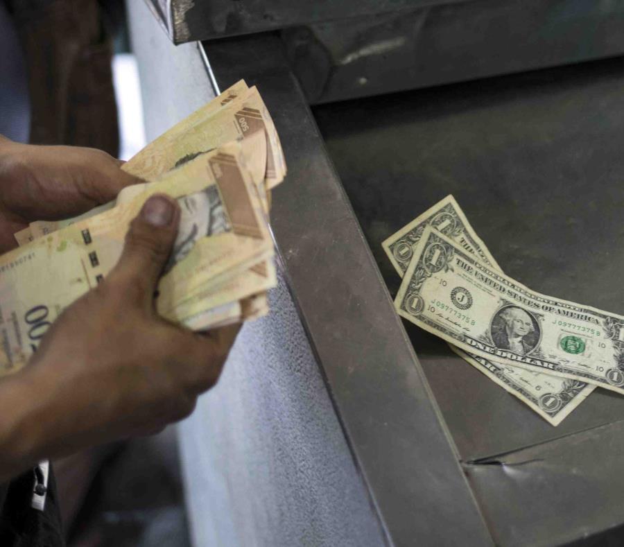 Una persona cuenta sus dólares y bolívares para pagar productos en un mercado en Caracas. (AP/Rodrigo Abd) (semisquare-x3)