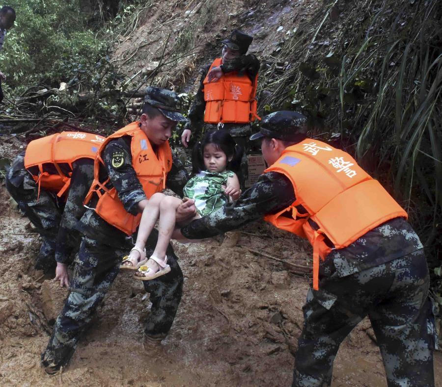 En esta foto del 8 de junio de 2019 difundida por la agencia noticias Xinhua se ve a socorristas ayudando a una niña en la villa Shanxi, China, luego de las fuertes lluvias en la zona. (Peng Zhaozhi/Xinhua vía AP) (semisquare-x3)