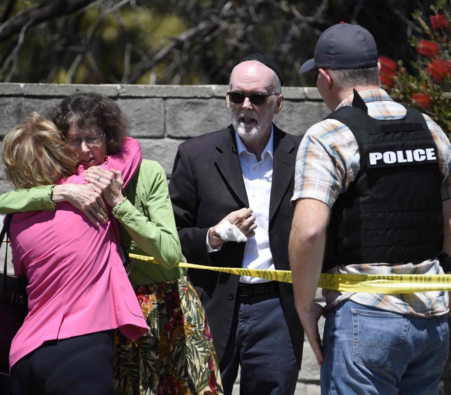 Feligreses caminan en las afueras de la sinagoga tras el tiroteo que hirió a al menos cuatro personas. (AP/ Denis Poroy) (semisquare-x3)
