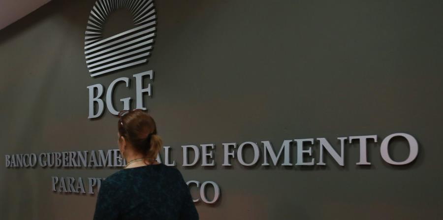 Una mujer camina frente al logo del Banco Gubernamental de Fomento. (GFR Media) (horizontal-x3)