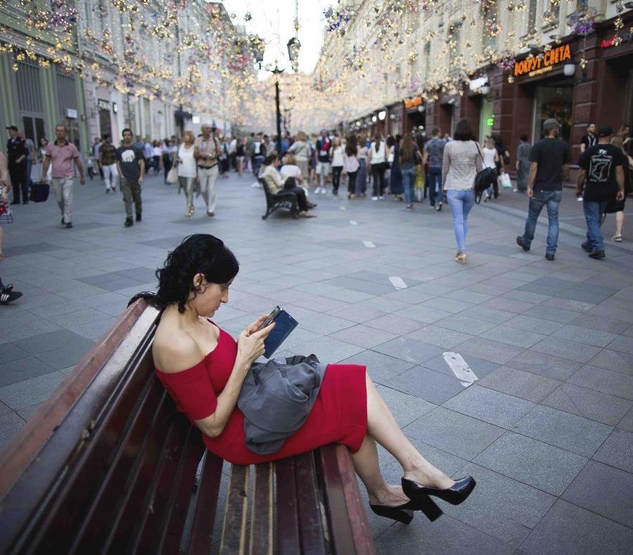 Una mujer observa su teléfono celular en la calle Nikolskaya, favorita de los fanáticos del fútbol, cerca de la Plaza Roja. (AP) (semisquare-x3)