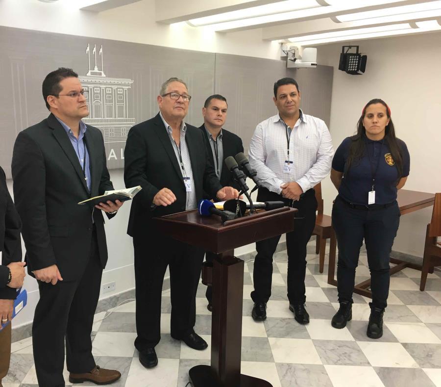 Al centro, José Tirado, presidente del Sindicato de Bomberos, durante una conferencia de prensa en La Fortaleza. (semisquare-x3)