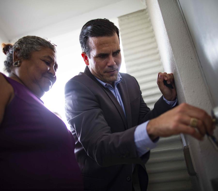 El gobernador Ricardo Rosselló ayuda a una señora a abrir la puerta de su nuevo hogar. (semisquare-x3)