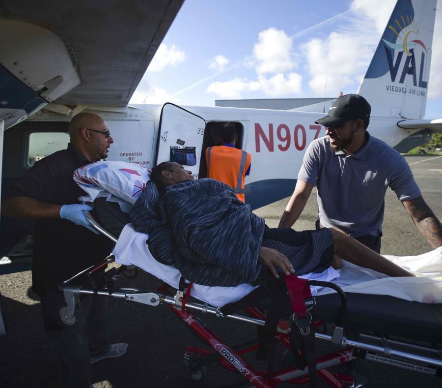 Paramédicos meten a Sandra Medina, una paciente de diálisis de 42 años, en un avión en Vieques, antes de viajar a Ceiba para recibir tratamiento en la clínica Fresenius de Humacao. (AP) (semisquare-x3)