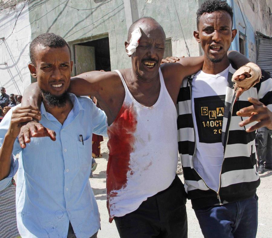 Unos jóvenes ayudan a un homre que resultó herido tras la explosión. (semisquare-x3)