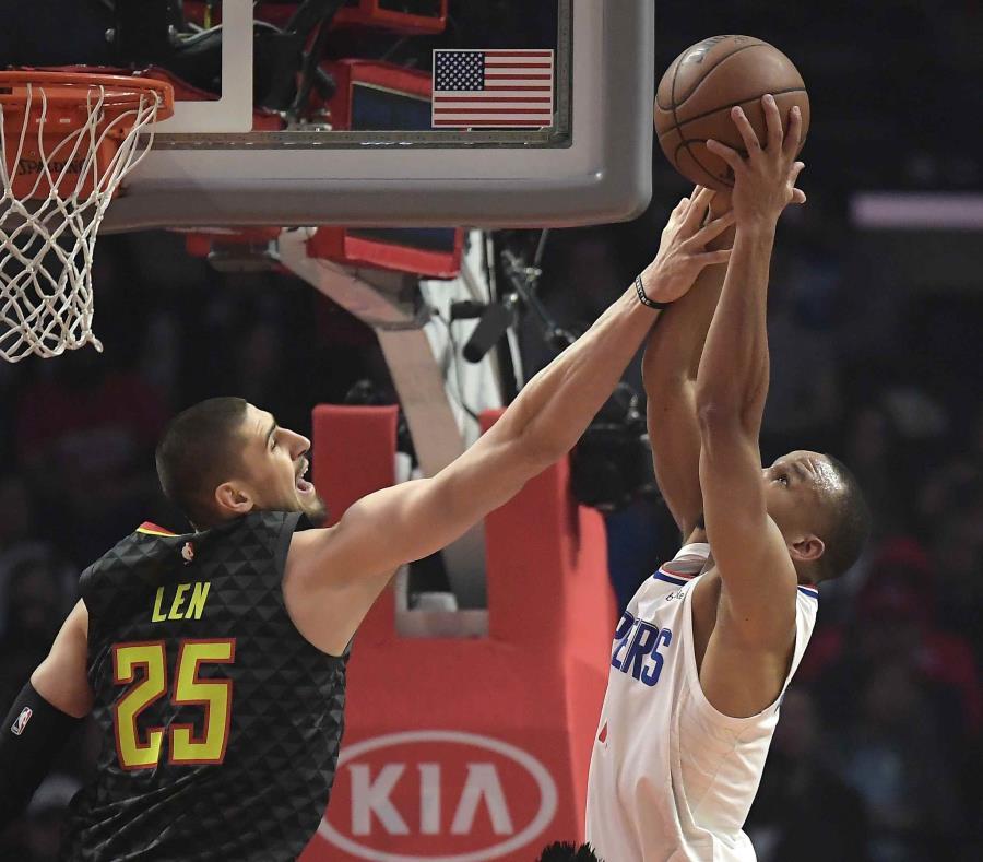 El jugador de los Hawks de Atlanta Alex Len (izquierda) y su rival de los Clippers de Los Ángeles Avery Bradley alcanzan un rebote durante la primera mitad del juego de la NBA que enfrentó a ambos equipos. (AP Foto/Mark J. Terrill) (semisquare-x3)