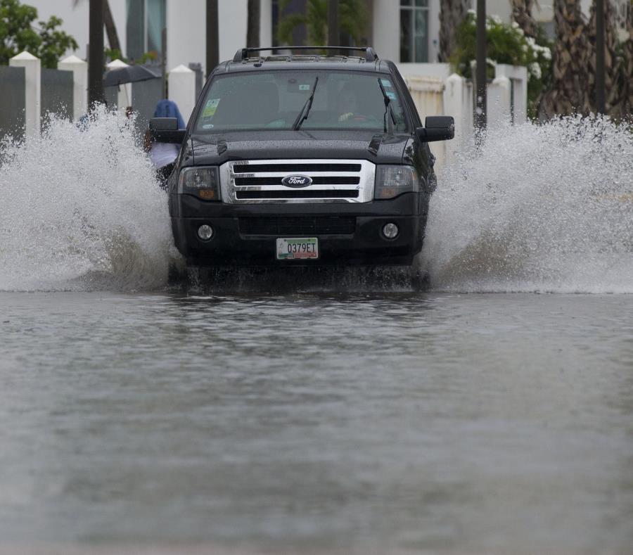 Una guagua pasa por un área inundada, mientras unas mujeres se mojan mientras caminan por la acera. (GFR Media) (semisquare-x3)