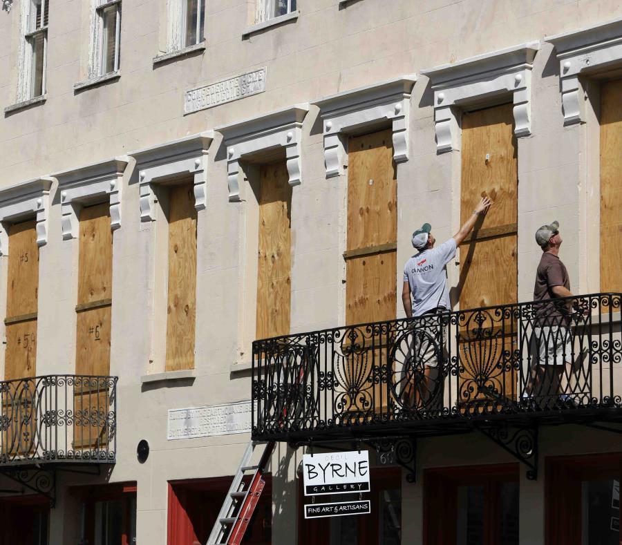 Dos personas colocan paneles de madera en Confederate House en el centro de la ciudad de Charleston, en Carolina del Sur. (AP) (semisquare-x3)