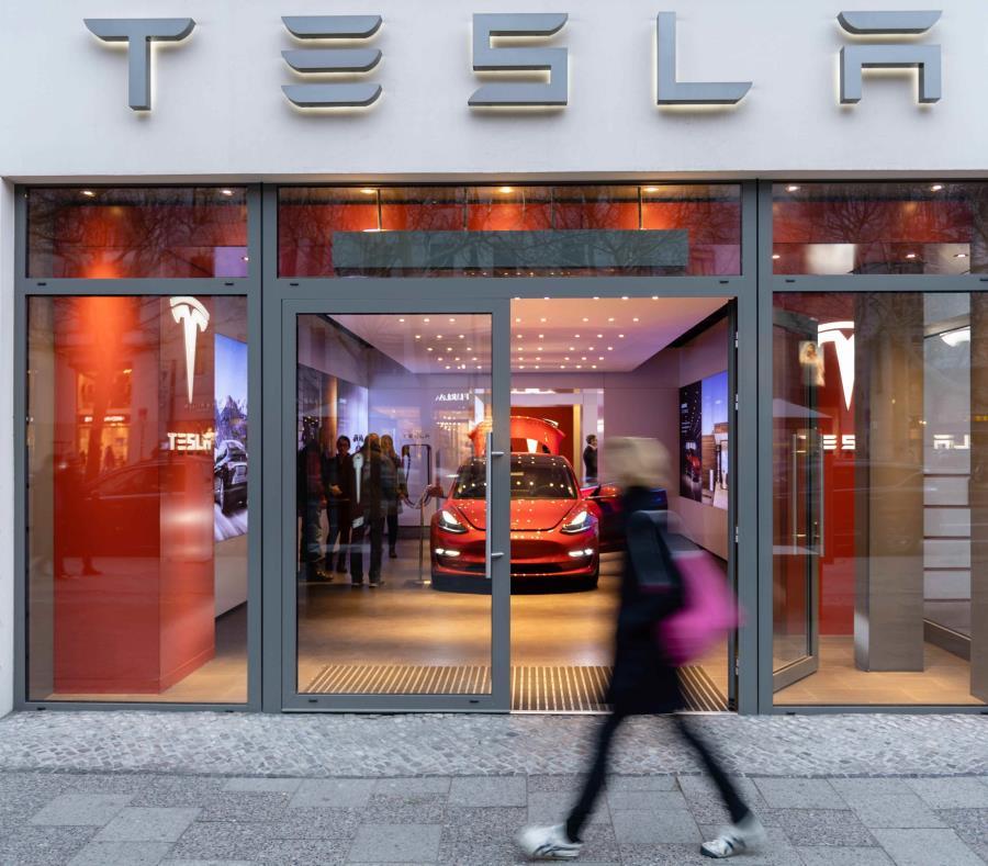 Una mujer camina junto a un sala de exposición de la compañía de vehículos Tesla, en Berlín. (EFE / Jens Schlueter) (semisquare-x3)