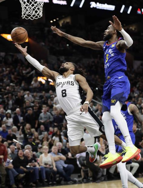 El base de los Spurs de San Antonio Patty Mills ataca el canasto y supera al escolta de los Nuggets de Denver Will Barton. (AP / Eric Gay) (vertical-x1)