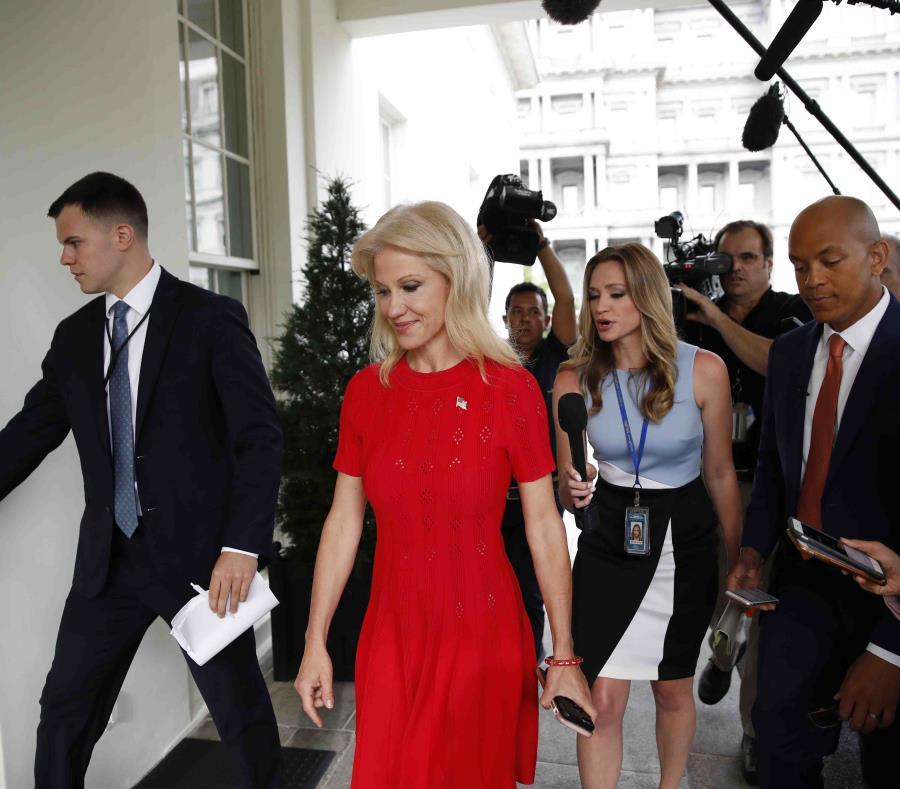 Kellyanne Conway, consejera del presidente Donald Trump, (traje rojo) va camino a una reunión con el primer mandatario estadounidense. (AP / Alex Brandon) (semisquare-x3)