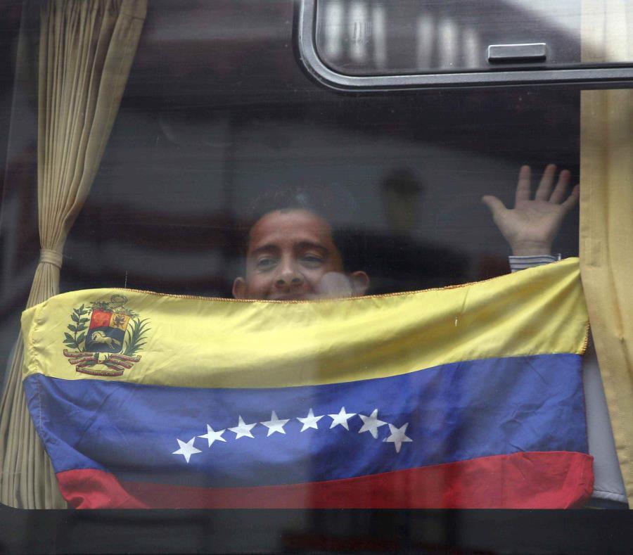 Un migrante venezolano con la bandera nacional saluda desde un bus que lo llevará al aeropuerto de Lima para el regreso a su país (semisquare-x3)