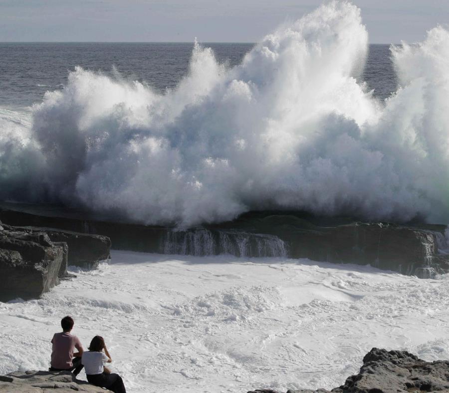 Una pareja observa el rompimiento de una ola en la ciudad costera de Shirahara. (Yosuke Mizuno / Kyodo News via AP) (semisquare-x3)