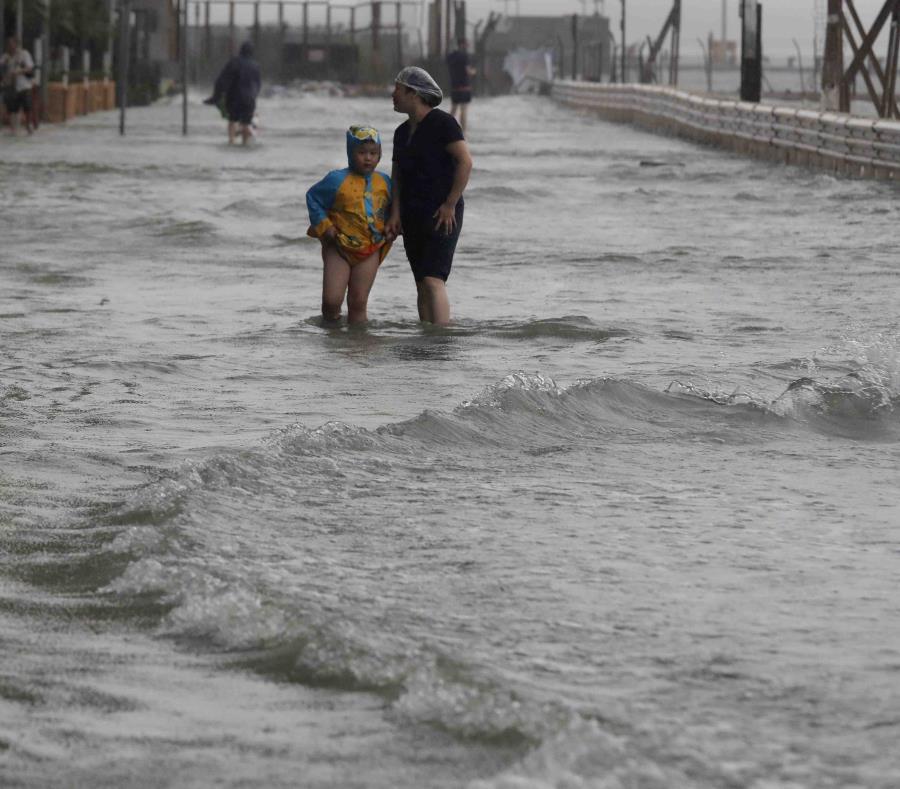 Unas personas caminan a través de una inundación causada por el tifón Mangkhut en Hong Kong, el domingo 16 de septiembre de 2018. (AP Foto/Vincent Yu) (semisquare-x3)