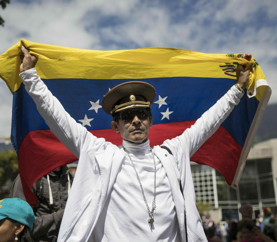 José Ramón Salas posa con una bandera de Venezuela y una gorra militar rusa en un mítin de la oposición para proponer leyes de amnistía para policías y soldados. (AP /Rodrigo Abd) (semisquare-x3)