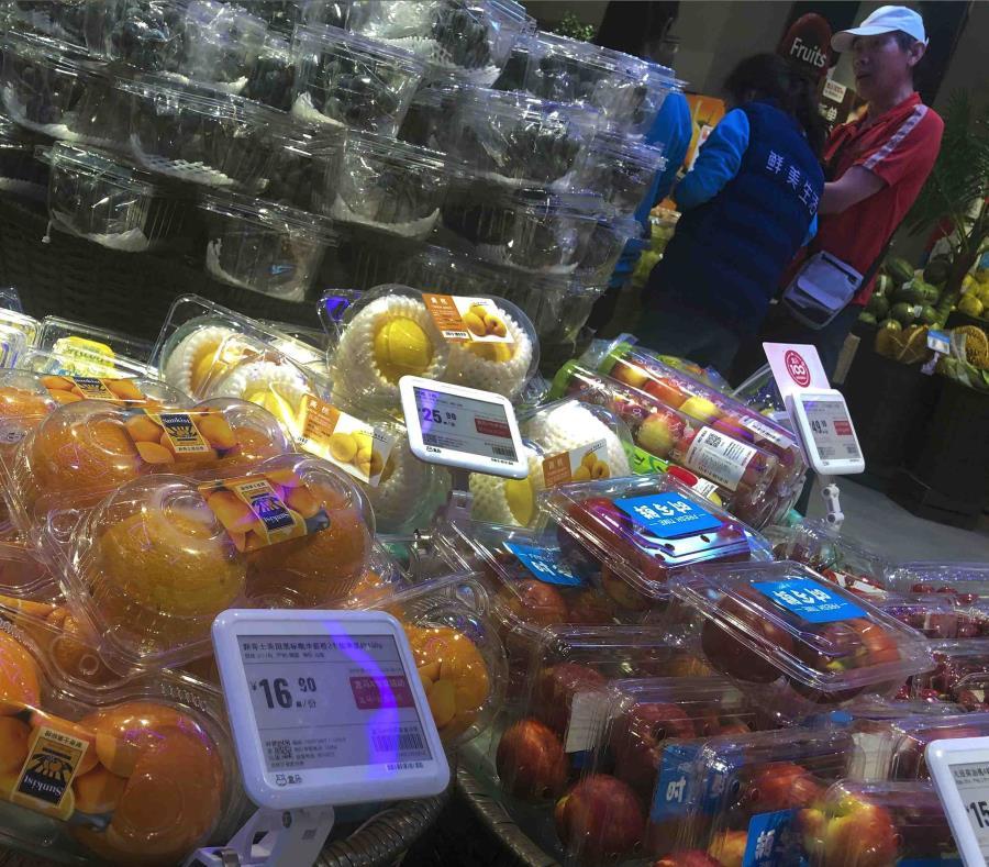 Un hombe charla con trabajadores cerca de una sección con fruta donde se ven naranjas de Estados Unidos y frutas de China en un supermercado de Beijing. (semisquare-x3)