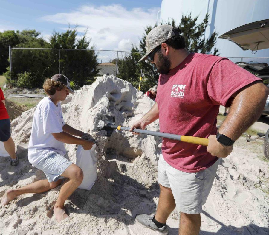Walker Townsend, de Isle of Palms, en Carolina del Sur, llena un saco de arena que sostiene Dalton Trout, en un estacionamiento municipal donde se reparte arena de forma gratuita dentro de los preparativos para la llegada del huracán Florence a la región. (semisquare-x3)