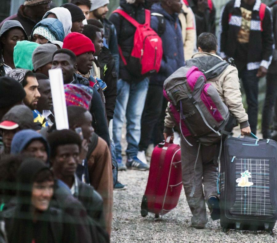 Varios migrantes esperan una cola en el centro de recepción de corta estancia (semisquare-x3)
