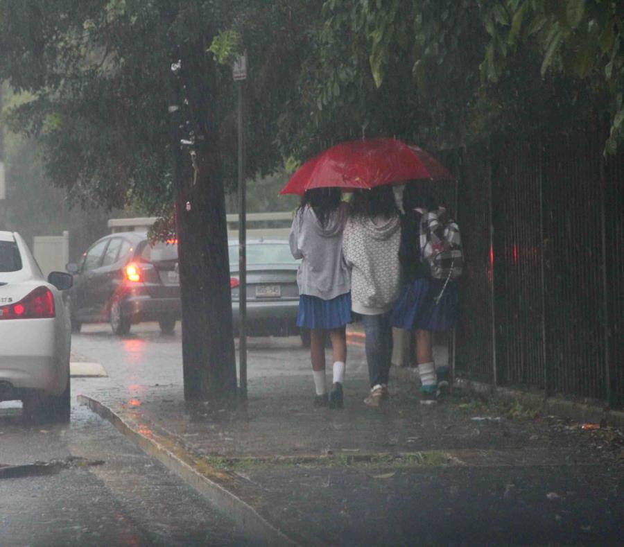 Unas estudiantes se escudan de la lluvia con una sombrilla. (GFR Media) (semisquare-x3)