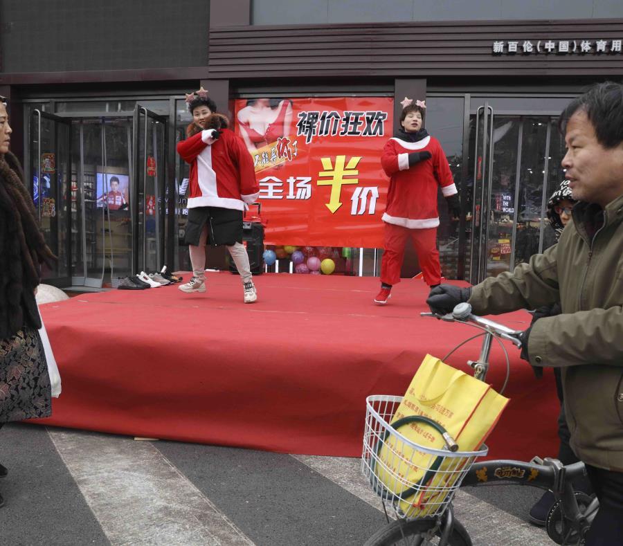 Esta foto del sábado 22 de diciembre del 2018, muestra a vendedores de una tienda con trajes de Santa Claus bailando para atraer clientes, en Zhangjiakou, provincia de Hebei, al norte de China. (AP) (semisquare-x3)