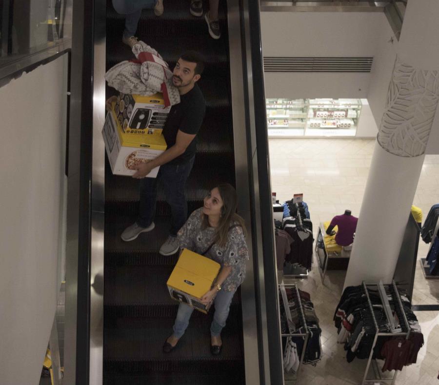 Dos personas bajan las escaleras de Macy's con varios Air Fryer. (semisquare-x3)