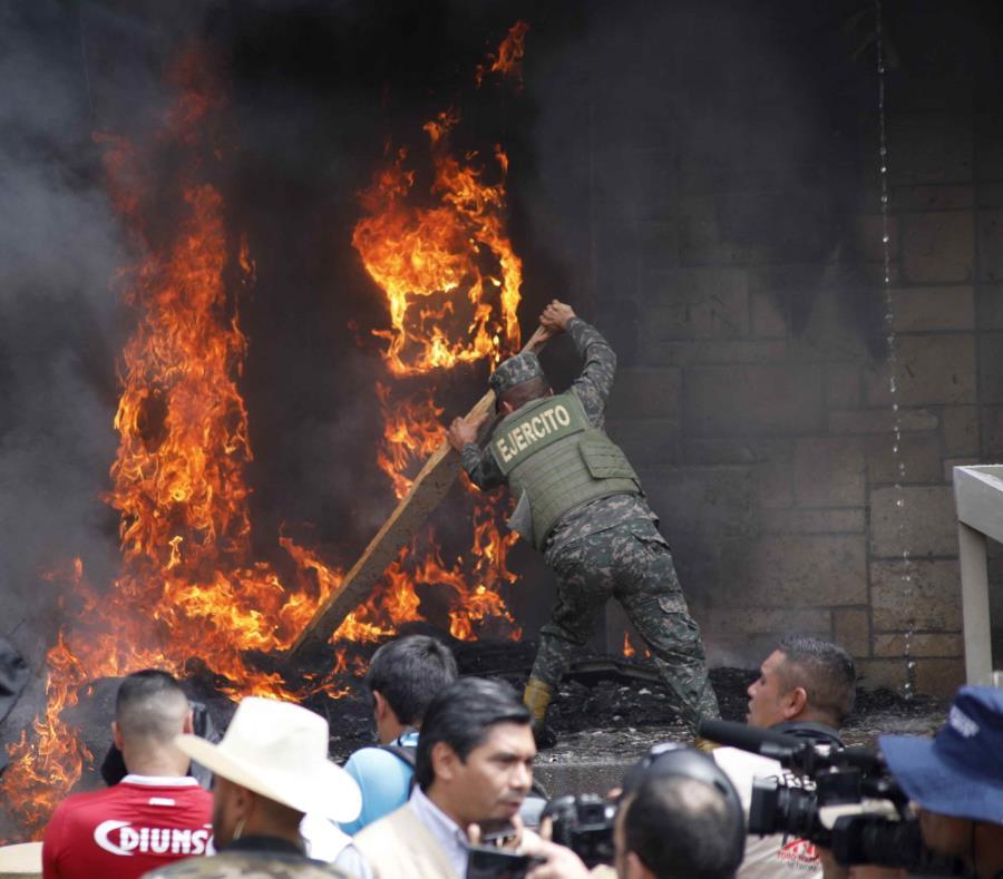 Un soldado intenta apagar el fuego frente a la embajada estadounidense en Honduras. (AP) (semisquare-x3)